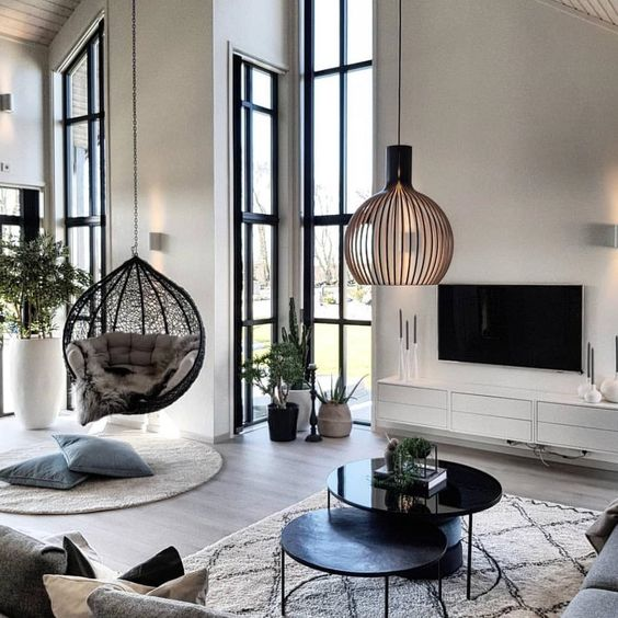 living room, wooden floor, black round nesting table, white rug, white wall, tall narrow glass window, rattan pendant, rattan swing, round rug, white floating shelves