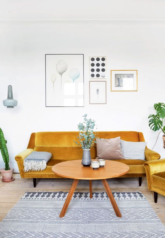 living room, wooden floor, grey rug, velvet yellow sofa and chair, white wall, sconce, round wooden coffee table