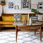 Living Room, Wooden Floor, White Rug, Brown Yellow Sofa, Round Coffee Table, White Wall, White Floating Shelves