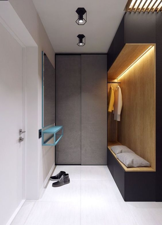 narrow entrance, grey cupboard, black nook with wooden inside, rail for clothes, LED ceiling lamp, mirror on the wall