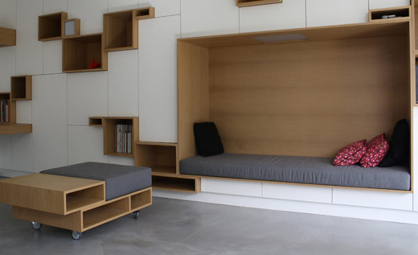 nook in the middle of white cupboard, wooden lines, wooden boxes for shelves inside, wooden nook with grey cushion