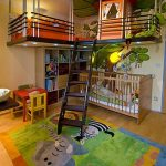 Nursery With Wooden Floor, Animal Printed Rug, White Wall, Wooden Cribs, Bed Upstairs, Dark Wooden Stairs, Tent, Low Talbe And Chair, Shelves