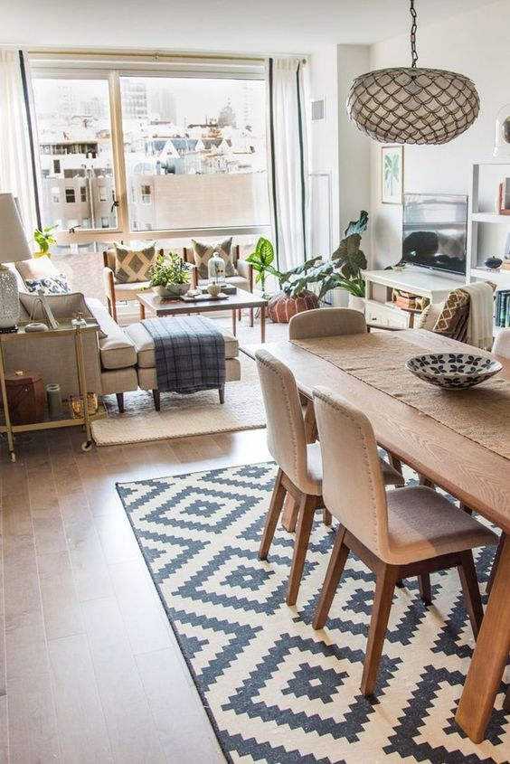 open living room, grey sofa with ottoman, grey small bench, coffee table, white table for TV, wooden table, wooden chairs with brown cushion, rug, pendant, white wall