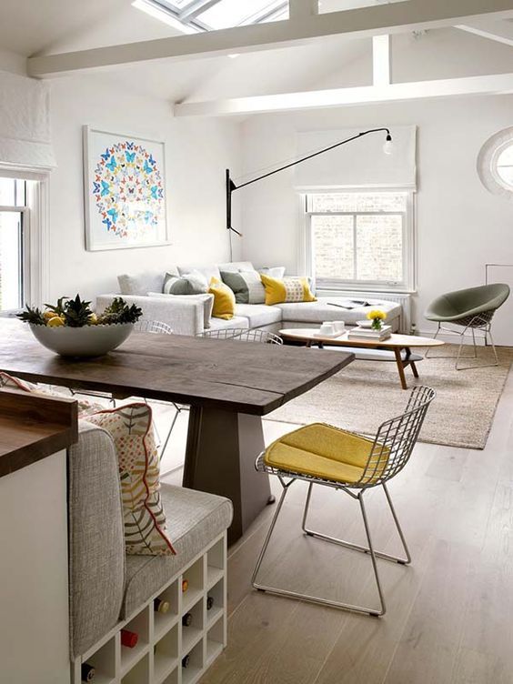 open living room, wooden floor, brown rug, white corner sofa, coffee table, dark wooden table, wire chair, white bench with grey cushion