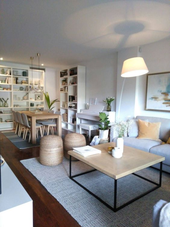 open living room, wooden floor, grey rug, white wall, white wooden bookcase, wooden tabl, modern chairs, rattan ottoman, wooden coffee table, pendants