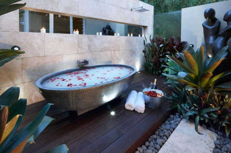outdoor bathroom ideas concrete freestanding tub wooden floor stone path outdoor plants mirror wall mounted tub filler frosted glass window outdoor lighting