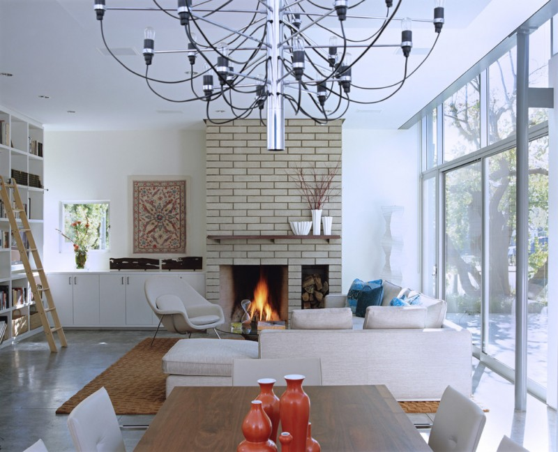 paint fireplace chandelier brown brick fireplace wall glass wall gray sectional sofa gray chair black glass coffee table brown rug white bookshelves ladder