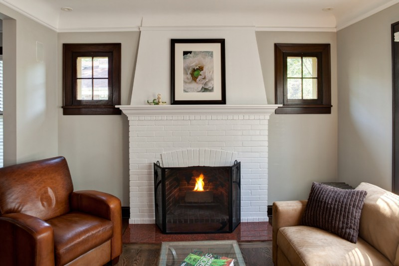 paint fireplace glass fireplace small windows white walls white brick fireplace white mantel brown leather sofa glass coffee table beige sofa pillows
