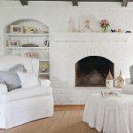 Paint Fireplace White Brick Wooden Floor Rattan Rug White Armchair White Skirt Lounge Chair White Built In Shelves Wood Beams Pillows