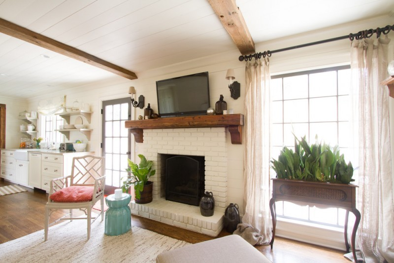 paint fireplace wooden beams white ceiling rug chair wooden planter drapes glass window glass door white cabinets wall sconces black rod