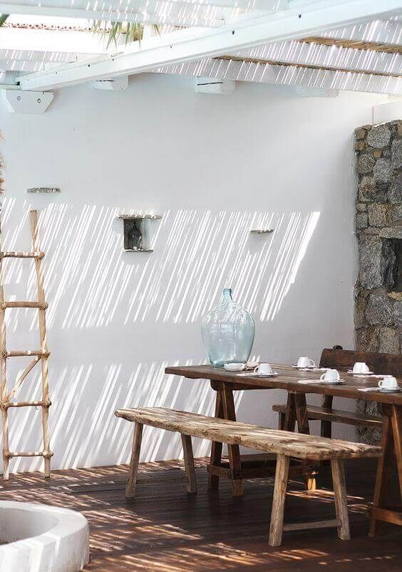 patio, wooden floor, white wall, natural stone wall, rattan ceiling, white wooden pergola, wooden table and bench