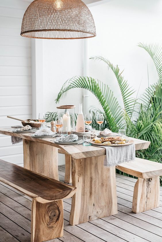 patio, wooden floor, white woodel wall, raw wooden table and bench, rattan pendant