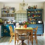 Pattern Floor Tiles And Backsplash, Blue Wooden Cabinet, Flower Curtain, Blue Wooden Shelves, Grey Floating Shelves, Chandelier, Wooden Table With Yellow Top, Wooden Chairs