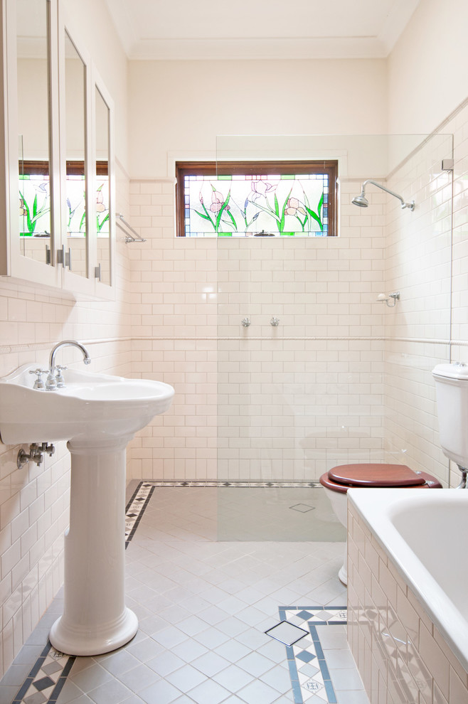 pedestal bathroom vanity glass window glass barrier white wall tiles built in tub gray floor tile mirrored cabinet towel rack shower head
