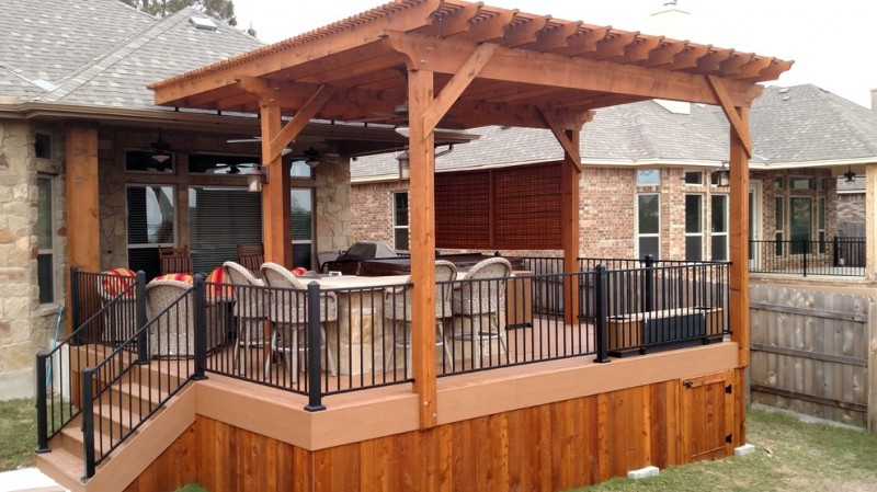 pergola on existing deck beige stairs black iron railing rustic rattan barstools outdoor chairs colorful cushions ceiling fan glass door