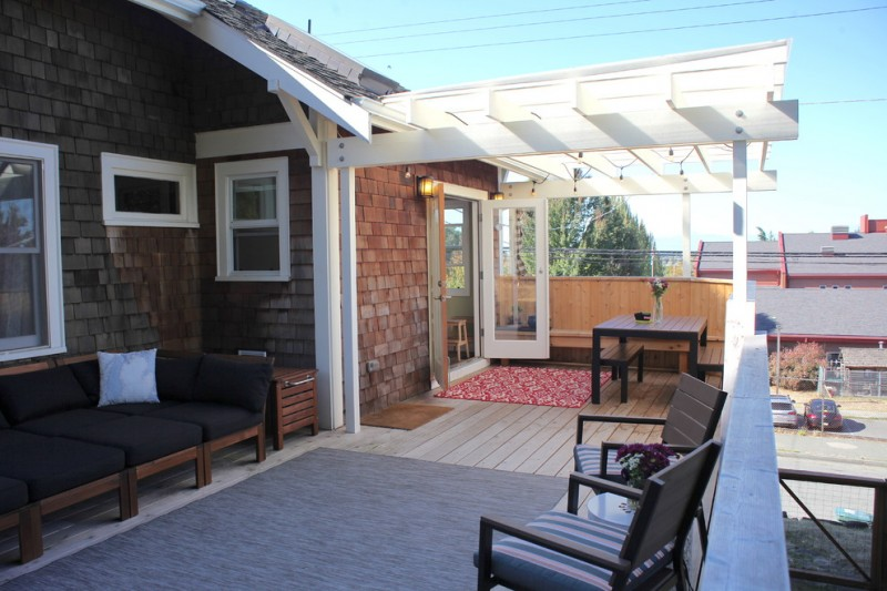 pergola on existing deck brick wall wooden floor wooden table wooden bench black cushions white glass windows area rugs glass doors wall sconces