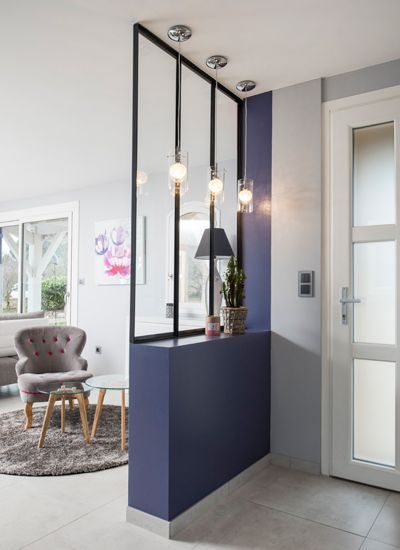 purple half wall, glass partition, pendants, pots, white floor, grey rug, grey chair, round nesting coffee table