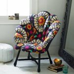 Shell Chair With Flowery Pattern And Wooden Legs, Wooden Floor, Black Framed Mirror, White Ottoman, Window