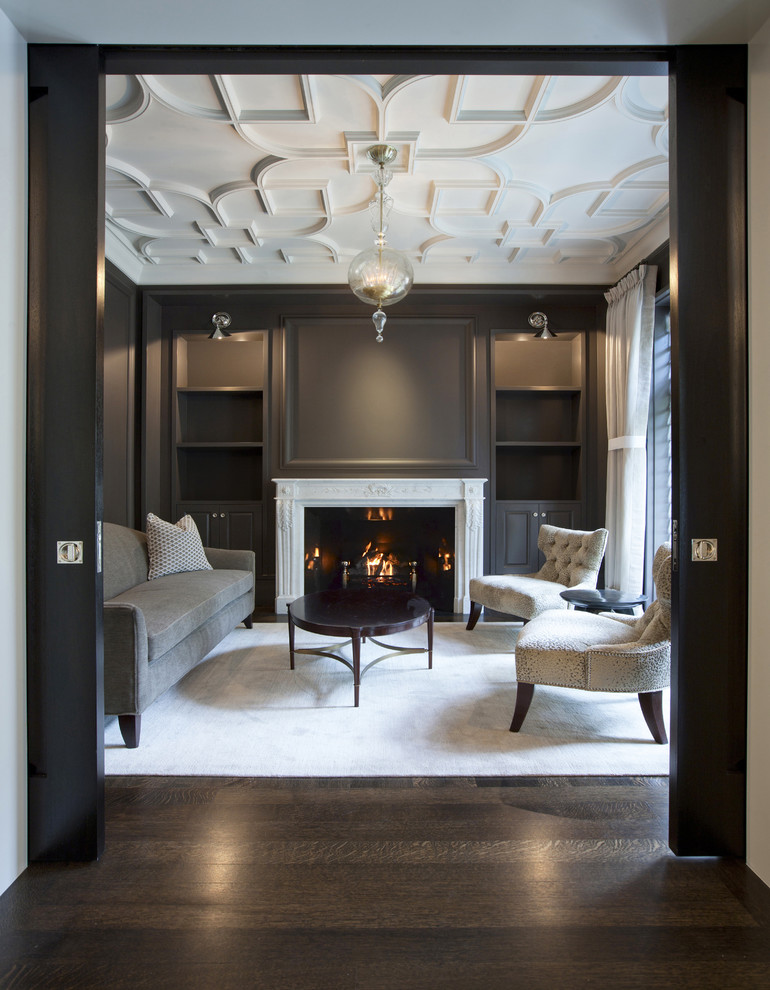 shiplap over fireplace dark wall glass chandelier white rug grey sofa tufted chair round coffee table white curtain white ceiling wall sconces ceiling molding windows