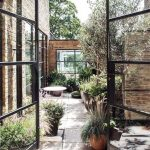 Small Backyard, Neutral Patio Floor, Plants On Pots, Wooden Wall, Glass Doors