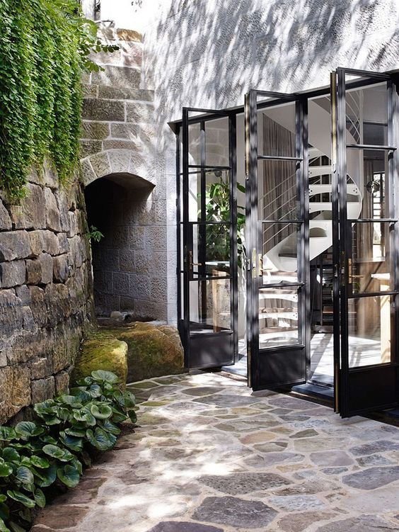 small garden, nautral stone floor, natural stone walls, plants from the top, few plants in the corner
