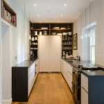 Small Kitchen Appliance Storage Glass Window White Pendant Lamps Black Countertop White And Black Cabinet Wooden Shelves Bookshelf Wooden Floor Stovetop