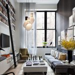 Small Living Room, Wooden Floor, Long Sofa, White Coffee Table, White Wall, Tall Glass Window, White Pendant, High Bookcase And Stairs, White Cabinet, TV, Black Wall