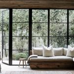 Small Long Garden With Plants, Glass Windows And Doors, Wooden Bench With White Cushion And Pillows
