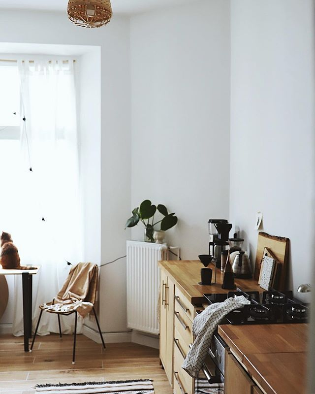 small long kitchen, wooden floor, natural wood look cabinet with wooden top, white wall, rattan pendant