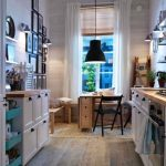 Small Long Kitchen, Wooden Floor, Rattan Rug, Wooden Dining Set With Benches, White Small Cabinet, White Drawers, Green Sliding Shelves, Black Pendant