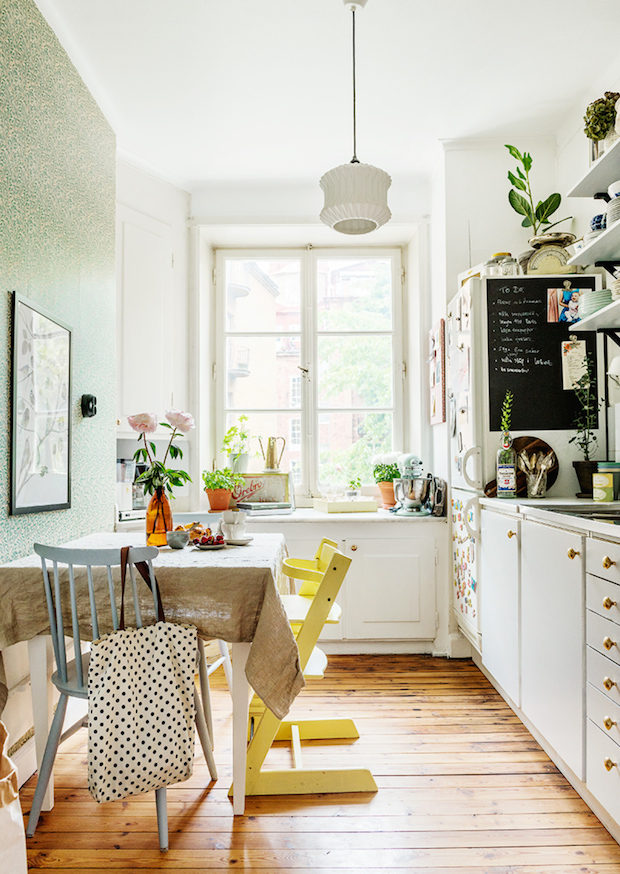 small long kitchen, wooden floor, white cabinet with golden knob, white wooden floating shelves, white pendant, white wooden dining table, yellow blue chairs
