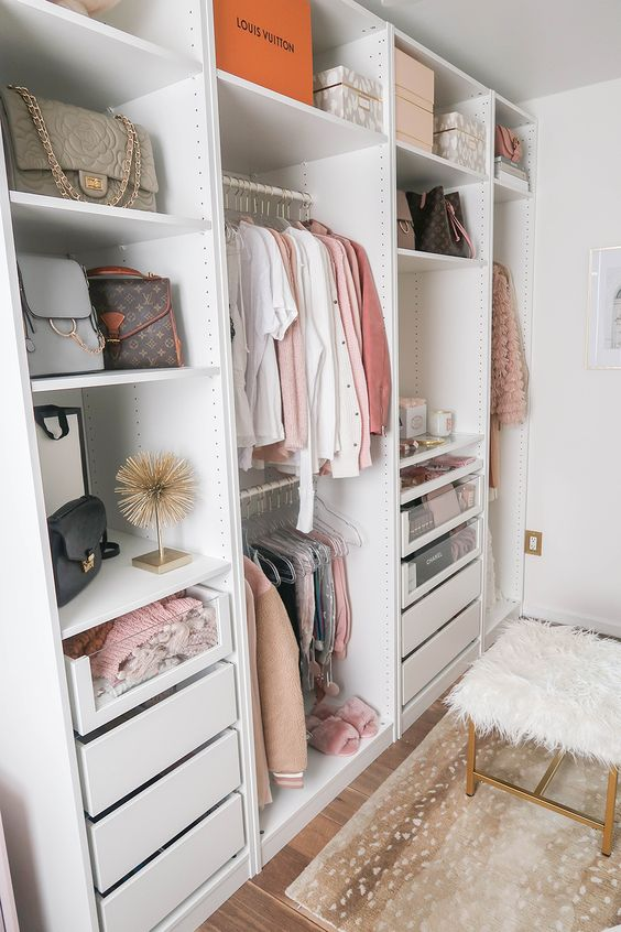 small walking closet with white cupboard with shelevs, drawers for clothes, and bags, wooden floor, stool with white fur