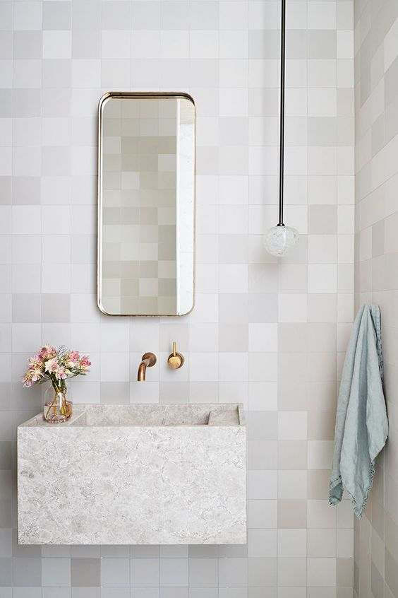 square tiles in many different hue of white colors, floating marble sink, golden faucet, bulbs pendant, mirror