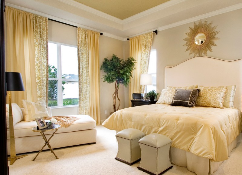 storage chaise beige bed headboars stools gold beddig sunburst wall mirror golden yellow curtains windows pillows floor lamp side table