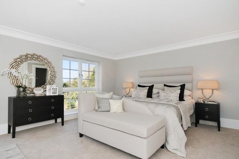storage chaise silk bedding grey headboard grey walls black nightstands black dresser round wall mirror white windows table lamps pillows