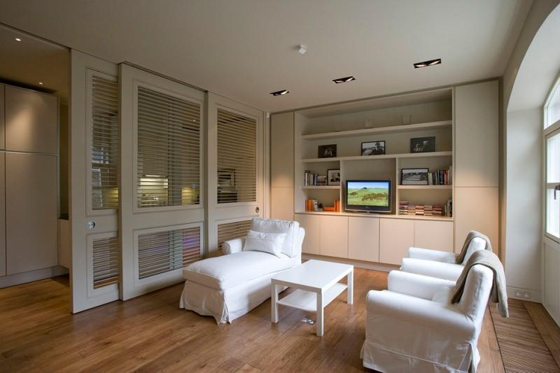 storage chaise white chaise white skirt armchairs white cabinet white shelves sliding glass doors wooden floor white coffee table glass windows