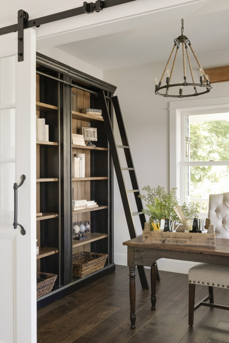 study room, wooden floor, wooden table, white studded chair, rustic chandelier, white wall, white ceiling, wooden books shelves.