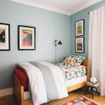 Superhero Room Wooden Bed Wooden Floor Colorful Rug Superhero Prints White Curtain Clorful Bedding Black Wall Sconce Teal Stool