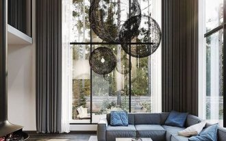 tall living room, wooden floor, rug, grey corner sofa, blue pillows, artistic pendants, tall and large glass windows, chair
