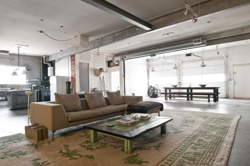 taupe sofa concrete floor large brown area rug vintage wooden coffee table throw floor lamp wooden dining table wooden benches industrial pendant lamps