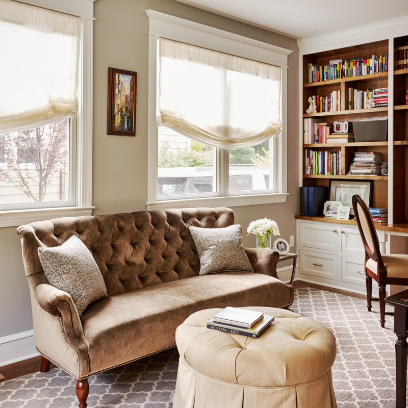 taupe sofa glass windows white shade grey area rug beige ottoman wooden bookshelves white drawers side table chair pillows