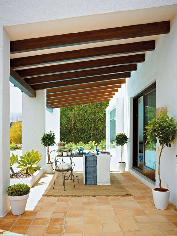 terrace, orange floor tiles, brown rug, table, black metal chair, white wall, wooden beams on the ceiling, white pots