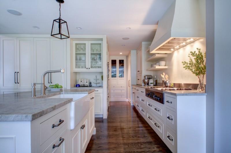 the sink glass iron pendant lamp white cabinet whte range hood stovetop white wall mounted shelves grey granite countertops faucet dishwasher white island