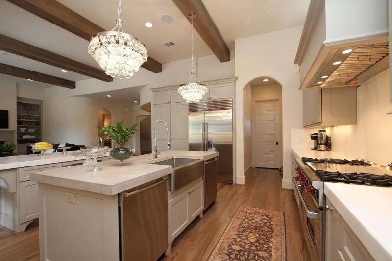 the sink white double island crystal chandeliers wooden floor kitchen rug stovetop oven range hood faucet white countertops fridge wood beams