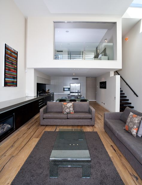 two levels apartment, white wall, wooden floor, grey sofa and rug, clear coffee table, kitchen and dining area under the upper level, bedroom upstairs with glass window