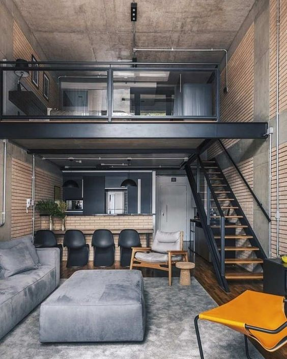 two levels apartment, wooden floor, bedroom on the upper evel with glass rail, living room with grey sofa, kitchen with open brick island and black chairs at the bottom