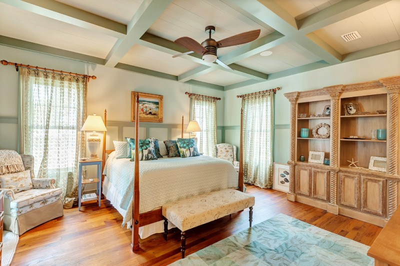 very narrow bedside table ceiling fan with light wooden bed bench pillows table lamps armchair windows curtains wooden floor area rug wooden cabinet