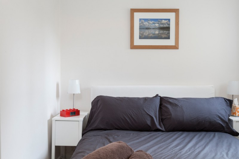 very narrow bedside table grey bedding grey pollows artwork white side table white table lamps white headboard