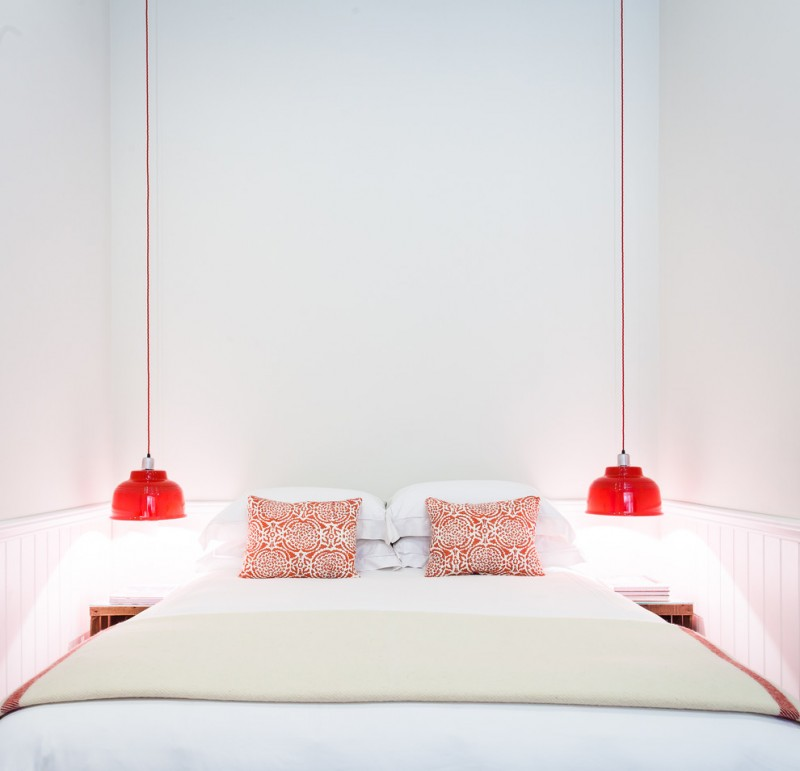 very narrow bedside table red pendant lamps red and white pillows white wall trim white walls white bedding shelves