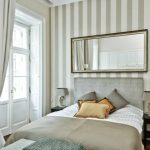 Very Narrow Bedside Table Wall Mirror Stripe Wallpaper Wall Sconce Grey Table Lamp Grey Headboard Bench Drapes White Glass Door